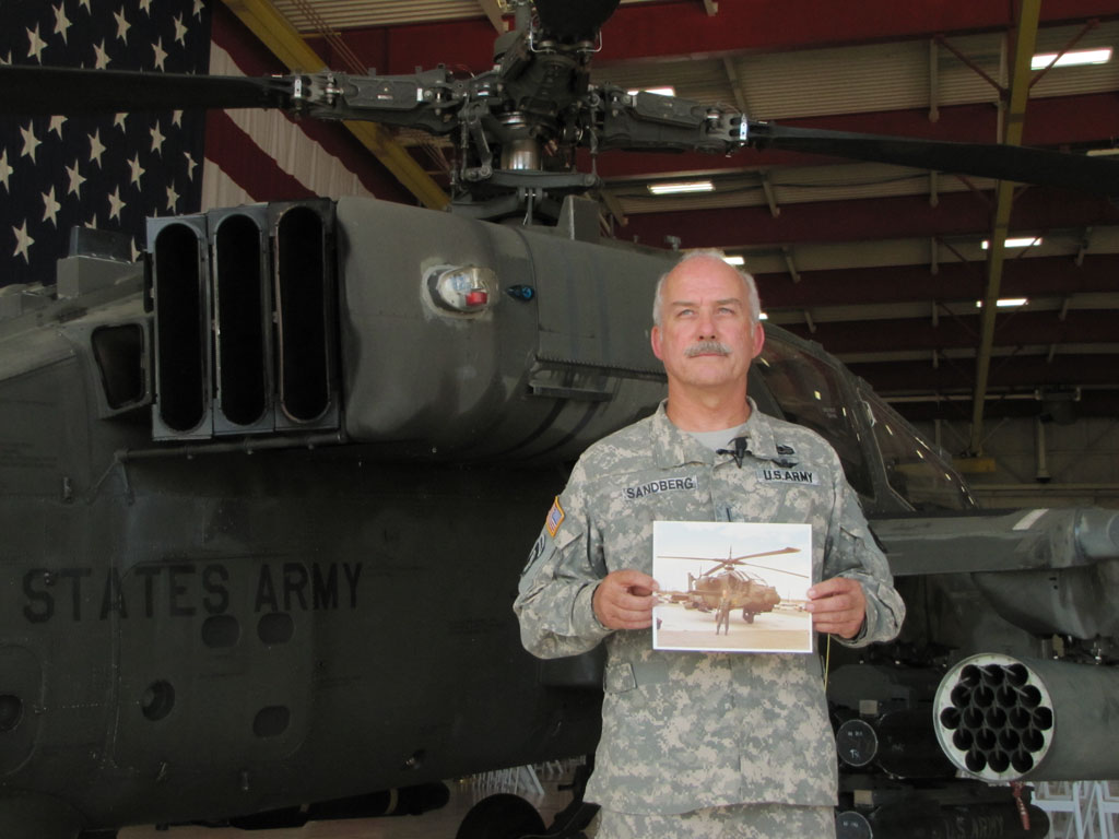CW5 Jim Sandberg, holds a photo of himself as a young pilot