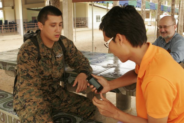 A U.S. Marine Corps petty interacts with a Thailand native using a translation application on a smartphone
