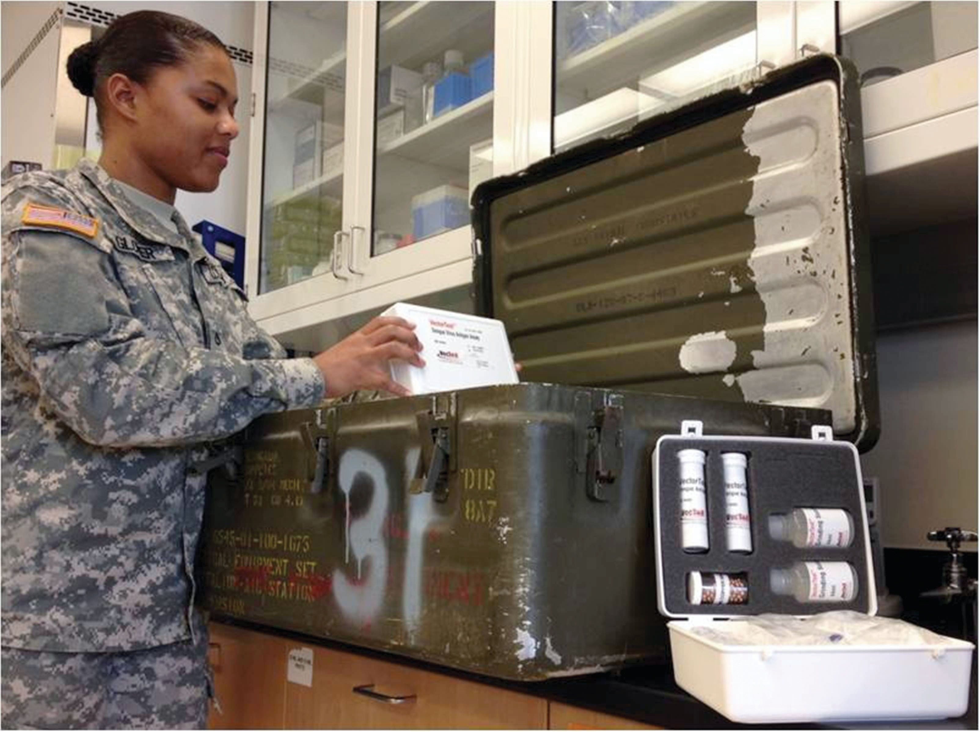 PFC Jessica Glover, a 68S preventive medicine specialist at WRAIR, loads the dengue AV-RDD kit into the Medical Equipment Set Entomological Lab. The kit is the outgrowth of an SBIR initiative begun in 2003. (Photo by Maj. Vanessa R. Melanson, WRAIR)