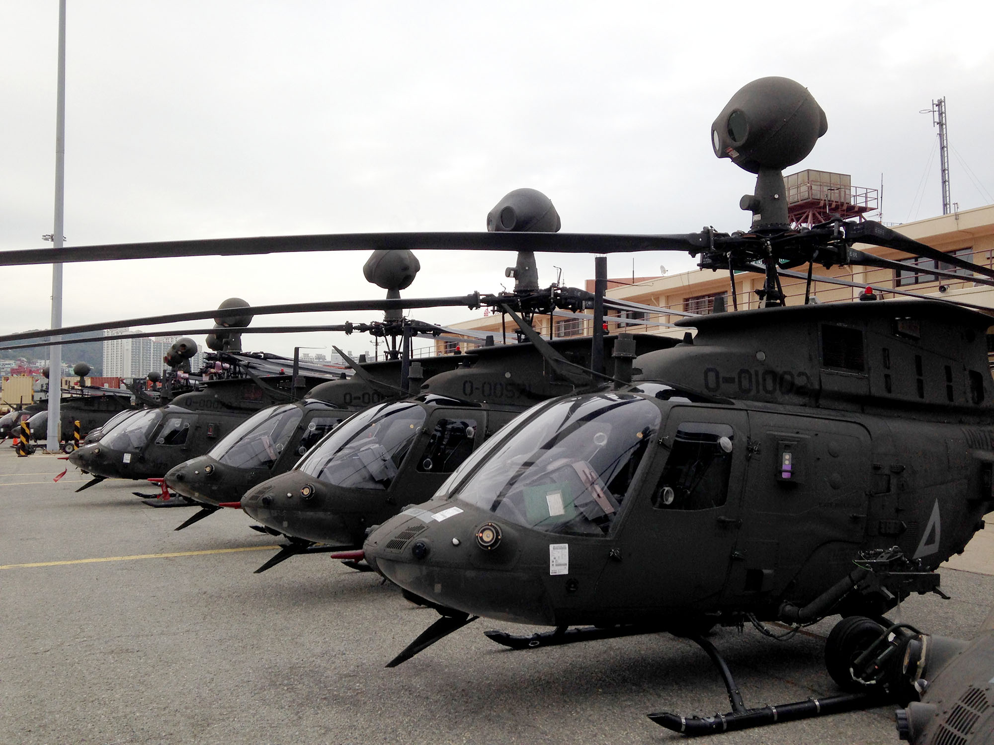 OH-58D Kiowa Warrior helicopters discharged from the Ocean Giant are staged at Pier 8