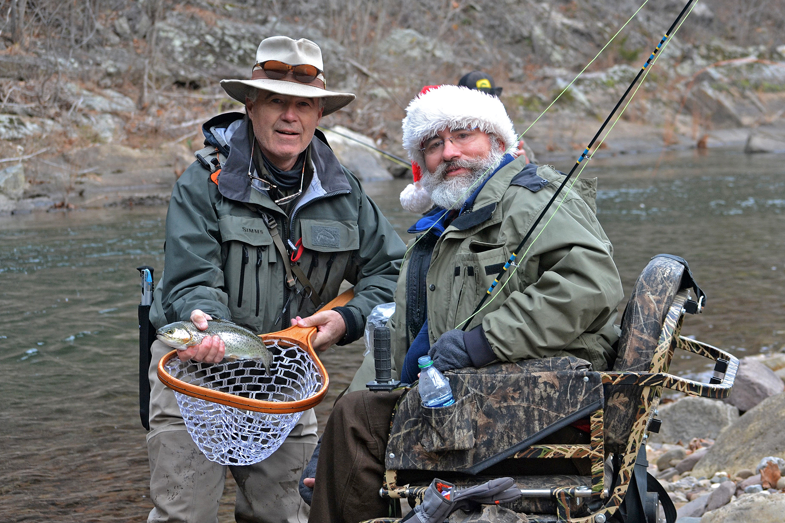 (left) PHWFF volunteer, Bruce Gilley, a veteran himself, helps (right) retired Maj. Rick Warrington and PHWFF Fort Belvoir participant land a trout during the Sixth Annual PHWFF Fly Fest at Harman's Luxury Log Cabins in Cabins, West Virginia, Dec. 2-4. The annual three-day event gives veterans and disabled service members an opportunity to fly fish with volunteer guides on the waters of the North Fork River. (photo by Juli Hedrick)