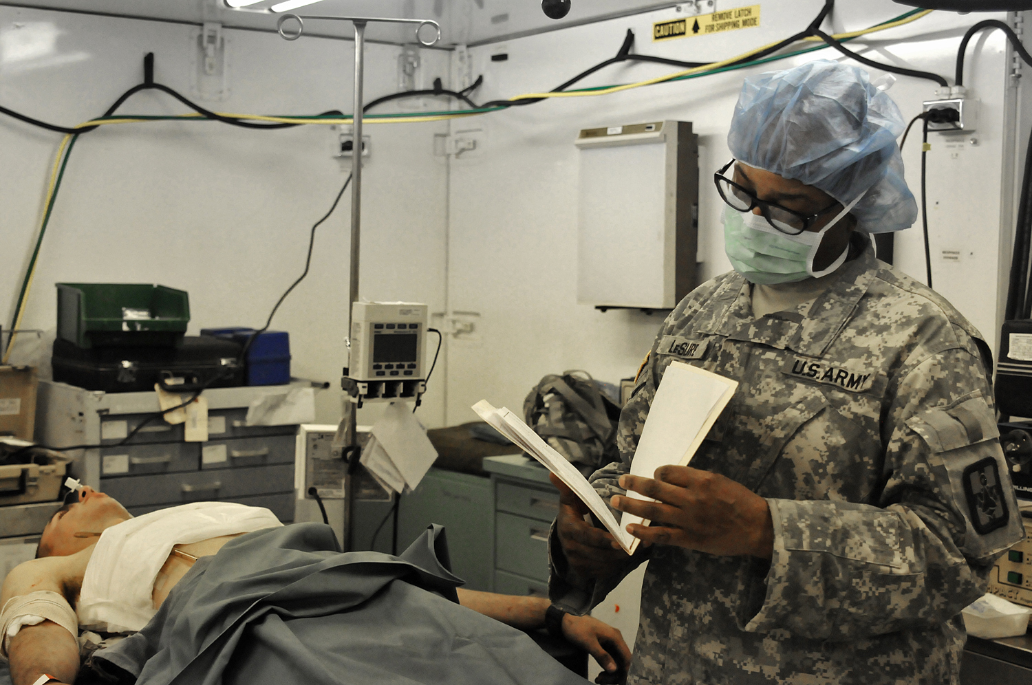 Lt. Col. Anita Lesure, a Soldier with the 801st CSH and head nurse of the operating room, examines a patient's chart to decide further treatment during a MASCAL exercise simulating a helicopter crash with 32 casualties at Fort Hunter Liggett, California in May 2016. Medics gave battlefield aid and evacuated the casualties to the CSH. (U.S. Army photo by Sgt. Kimberly Browne, 350th Public Affairs Detachment)