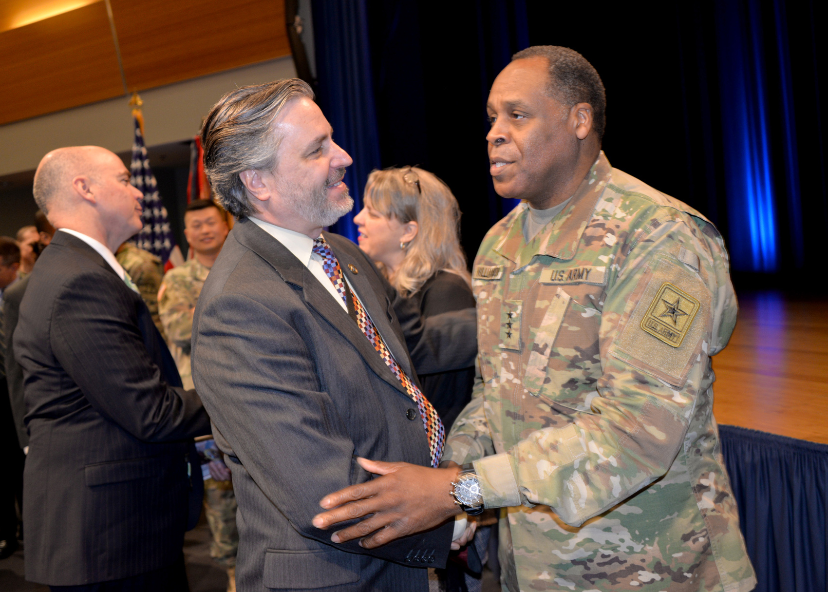 "Lt. Gen. Williamson greets Craig Spisak, director of the U.S. Army Acquisition Support Center and deputy director, acquisition career management, at the farewell ceremony. ""One of the prime things Lt. Gen. Williamson did when he came into this organization was care about people and start a number of efforts—all about talent management,"" said Spisak. (U.S. Army photo by Tara Clements/Released)"