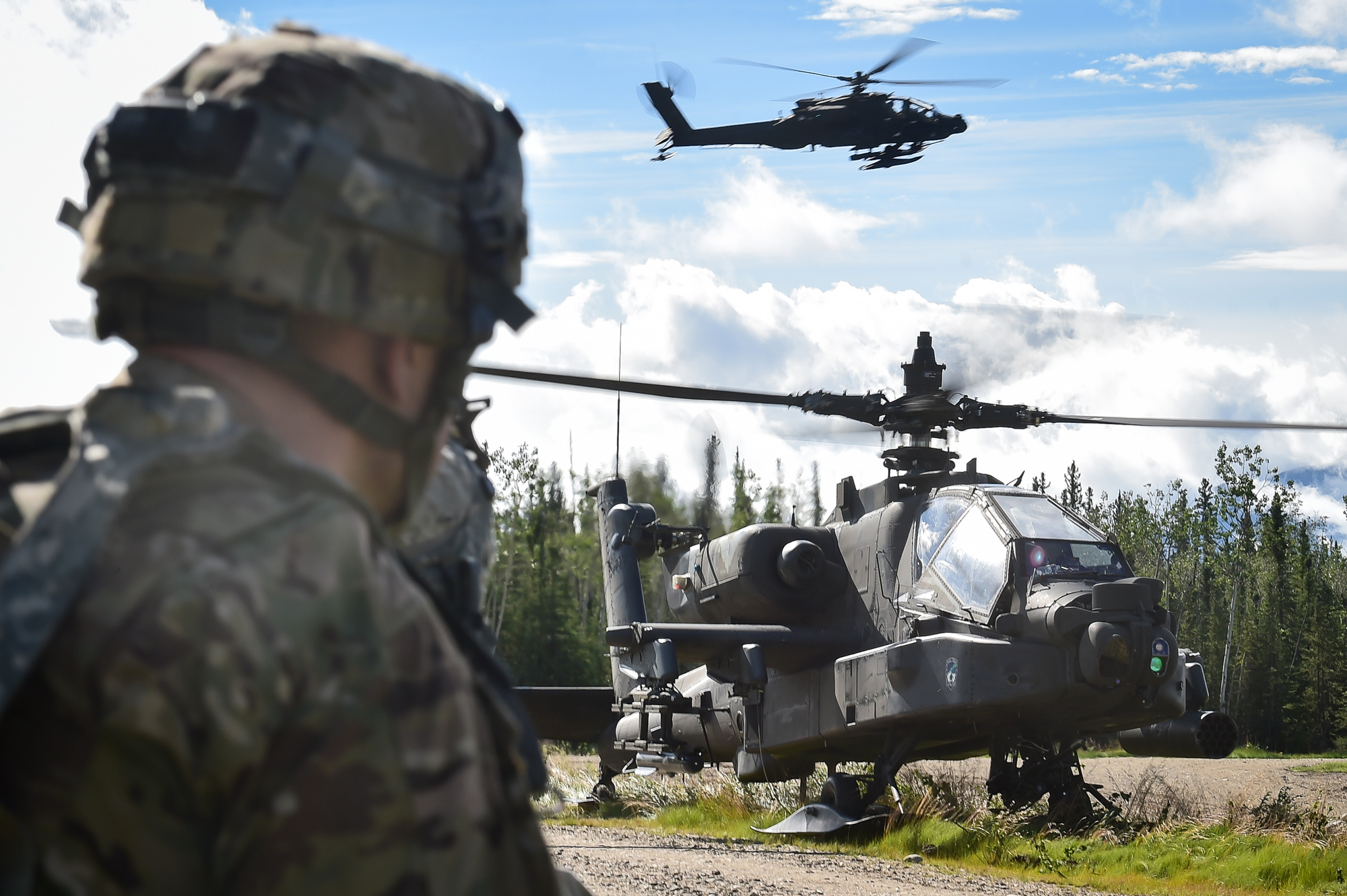 "An AH-64 Apache attack helicopter lands on a road as Soldiers radio reports during an opposing forces ""attack"" in July 2016 as part of Arctic Anvil 2016, an exercise in Donnelly Training Area near Fort Greely, Alaska. The exercise, the largest held in the interior of Alaska in 15 years, gave FAST advisers the opportunity to see what issues Soldiers experience with equipment and technology. (Photo by Justin Connaher, 673rd Air Base Wing, Joint Base Elmendorf-Richardson, Alaska)"