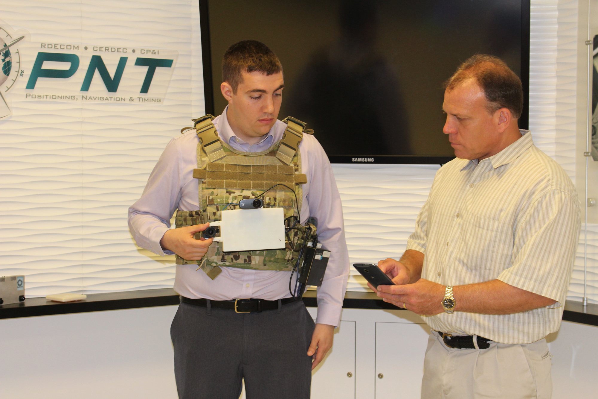 CERDEC engineers Eric Bickford, left, and Dr. Gary Katulka demonstrate a laboratory prototype of a vision-aided navigation system for dismounted Soldiers. PNT capabilities aid GPS when its signal becomes degraded or denied due to environmental or adversarial sources. Machine learning could insert intelligence into PNT systems so that Soldiers know which sensors are most reliable under any given circumstance. (U.S. Army photo by Kathryn Bailey, CERDEC)