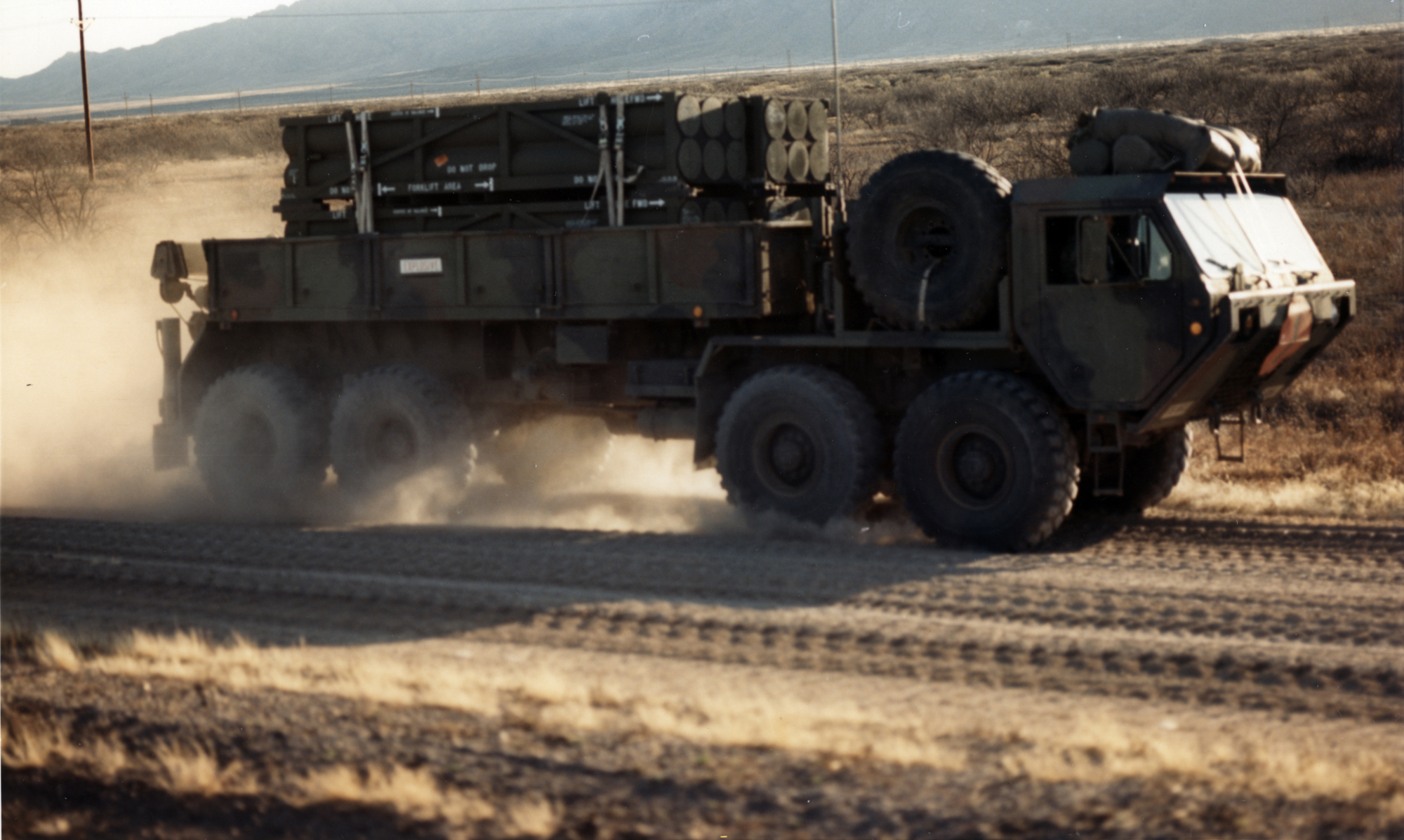 A Heavy Expanded Mobility Tactical Truck loaded with four missiles conducts mobility road testing and cargo handling on dirt roads at White Sands Missile Range in March 1990. Unlike with other elements of stress testing, the IOT&E for ATACMS marked the first time that the PMO transported the missiles on the truck, their designated prime mover, across rough terrain. However, DT environmental stress testing had been so rigorous that no related problems surfaced in IOT&E. (Photo by Tom Moore)