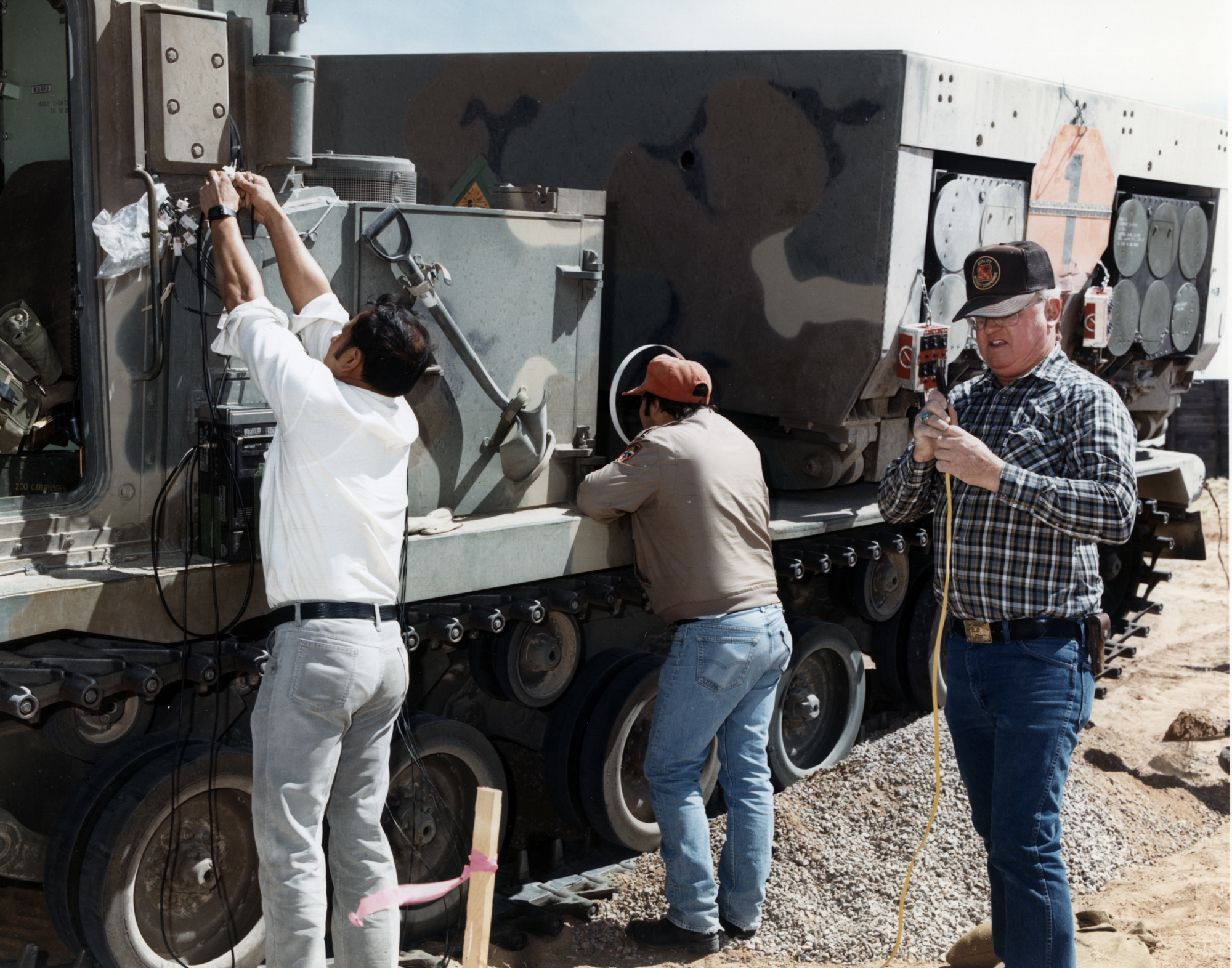 Contractor support personnel from SAIC install instrumentation and wiring on a Multiple Launch Rocket System launcher, the vehicular platform for the ATACMS, at White Sands Missile Range in March 1990. There were nine of the platforms to be used during the system's IOT&E. Instrumentation delayed the start of testing because of concerns about uncertified hardware being placed on the system. Lesson learned: Instrumentation was the single most important consideration that the Block I ATACMS program had neglected in development. PMs must plan for it well in advance to prevent testing delays. (Photo by Kenneth G. Schoultz)
