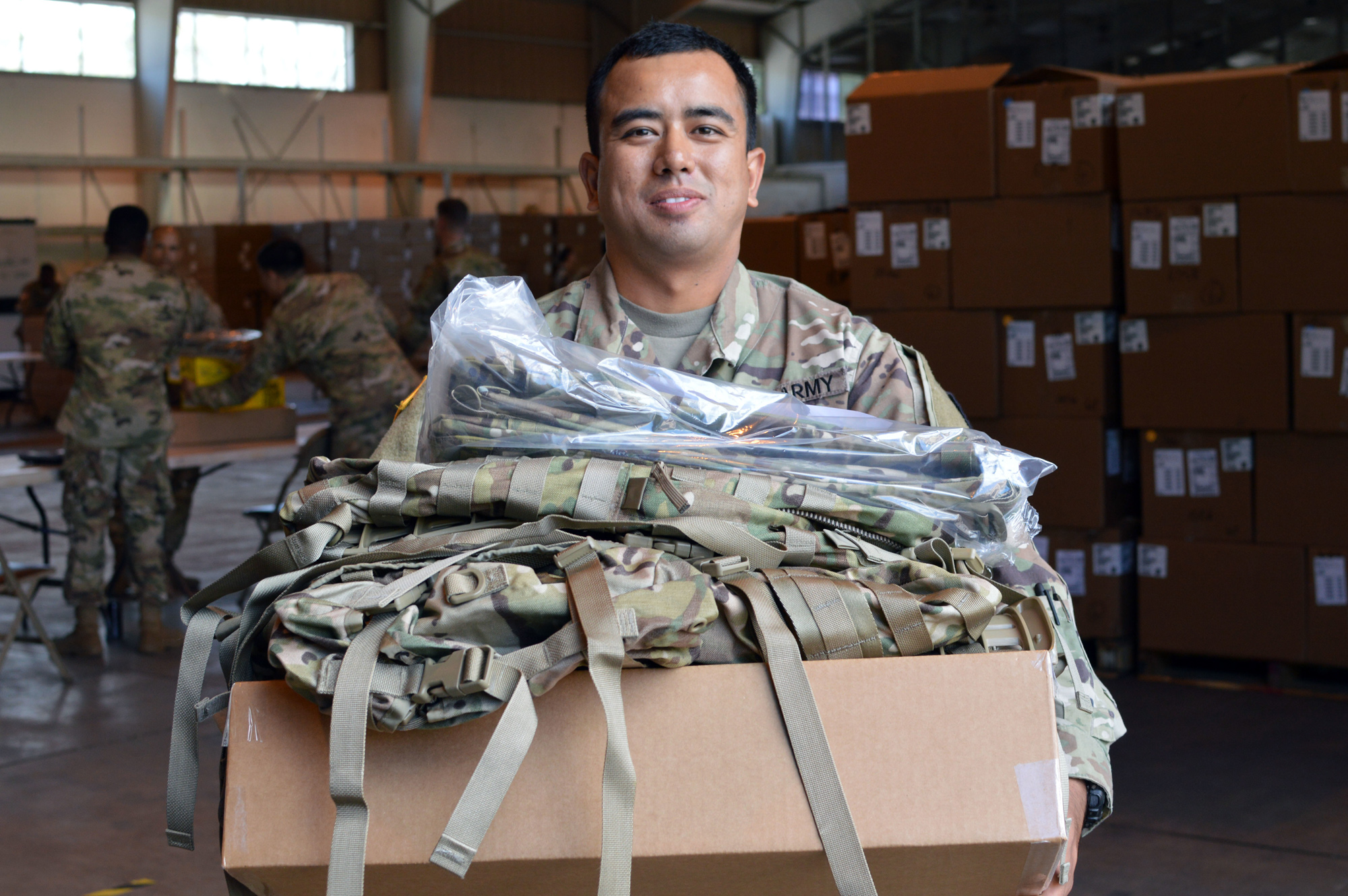 Spc. Saurav Udas, a supply specialist assigned to the 3rd BCT, 25th ID, holds new Operation Camouflage Pattern to be used in the tropical environments in the Pacific region. A program's schedule—how quickly the Army wants to get gear in the hands of Soldiers—requires considering return on investment. (U.S. Army photo by Staff Sgt. Armando R. Limon, 3rd BCT, 25th ID)