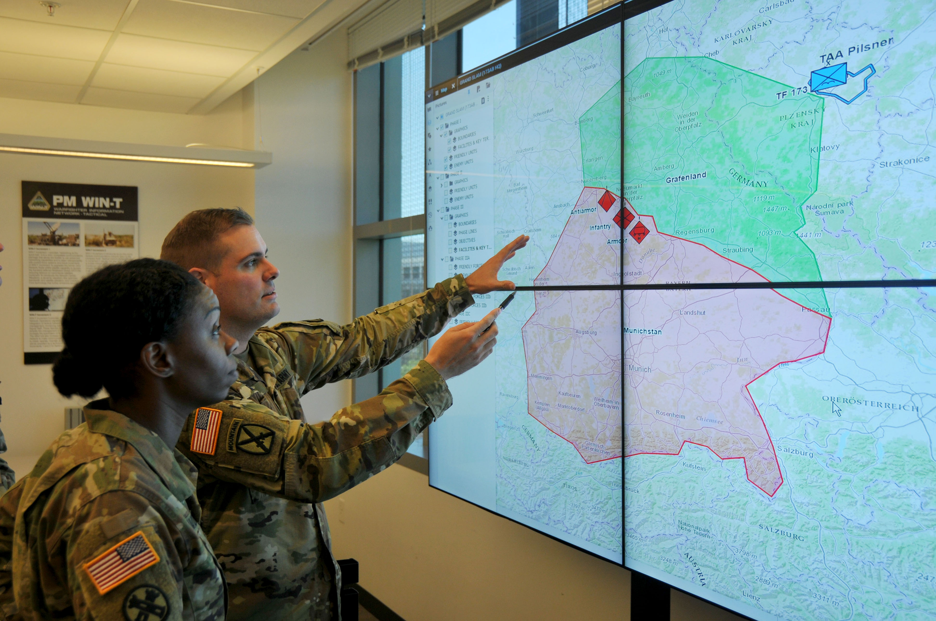 Maj. Summer Favors and Capt. John (Mack) Turner, assistant product managers for Project Manager Mission Command, review the common map for the Command Post Computing Environment, or CPCE. The Automated Planning framework will transition to the CPCE to help facilitate the Military Decision Making Process for commanders and staff. (Photo Credit: (Photo Credit U.S. Army PhotoDan LaFontaine, PEO C3T))