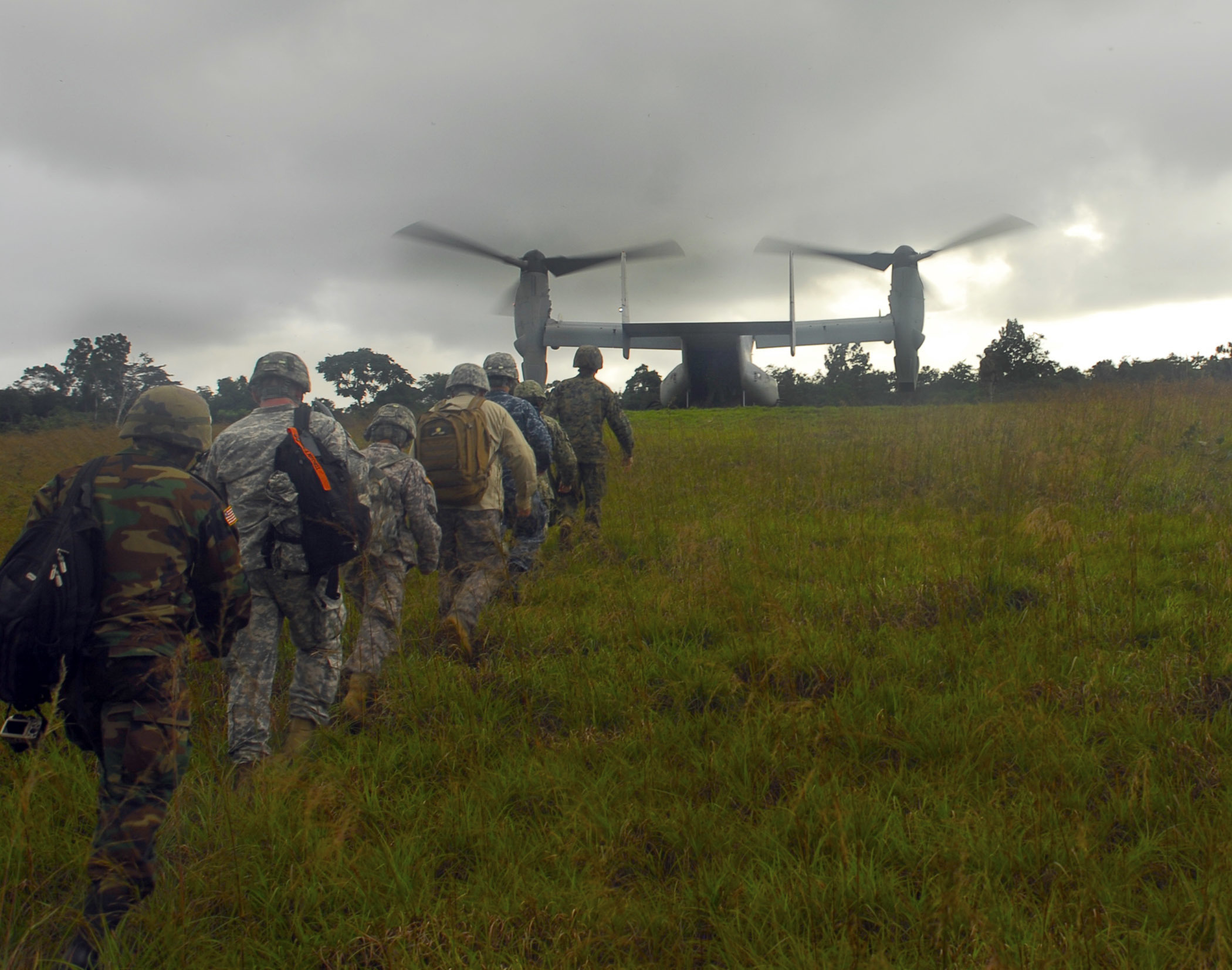 """U.S. Army and Marine Corps personnel prepare to board a U.S. Marine Corps MV-22 aircraft in October 2014 after surveying the site of a future Ebola treatment unit near Barclayville, Liberia. The U.S. military forces in West Africa during the Ebola outbreak worked well with the civilian machinery running the response, Aylward says, adding that U.S. aircraft """"came in real handy getting out to some of these remote areas."""" (U.S. Army Africa photo by Pfc. Craig Philbrick)"""