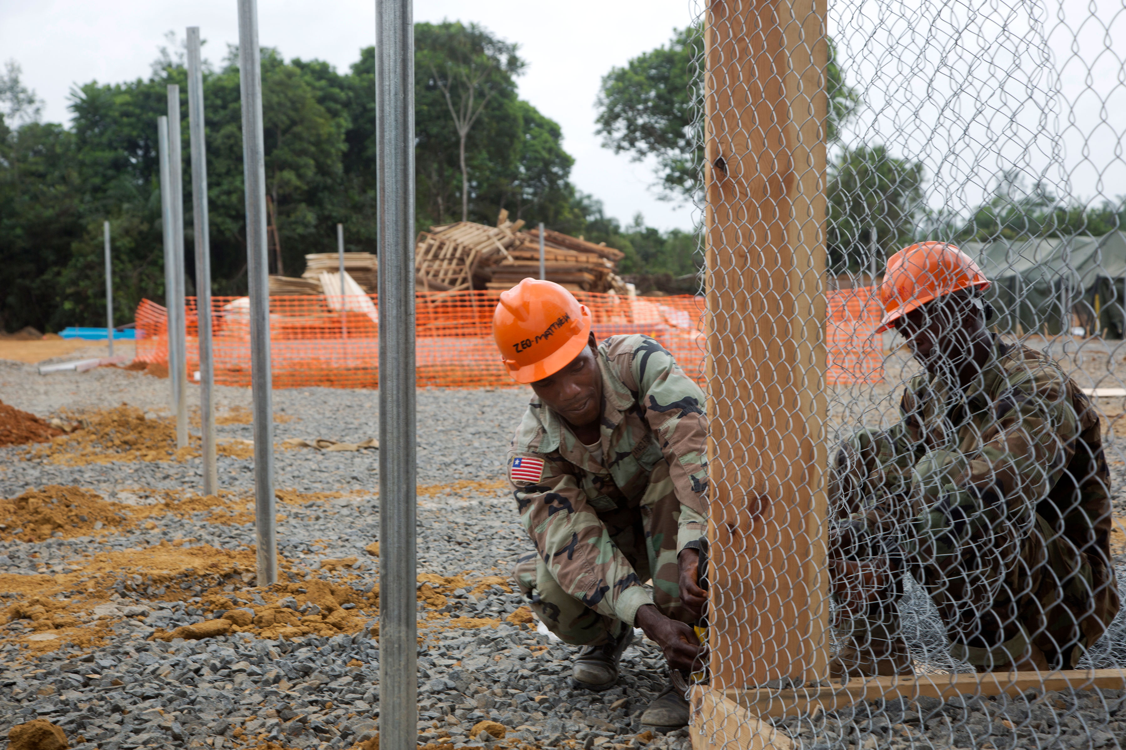 Liberian Soldiers attach fencing at an Ebola treatment unit being built in support of Operation United Assistance in Gbediah, Liberia, in December 2014. United Assistance was the DOD operation to provide command and control, logistics, training and engineering support to U.S. Agency for International Development-led efforts to contain the Ebola virus outbreak in West Africa. (U.S. Army photo by Sgt. 1st Class Brien Vorhees, 55th Signal Company (Combat Camera))