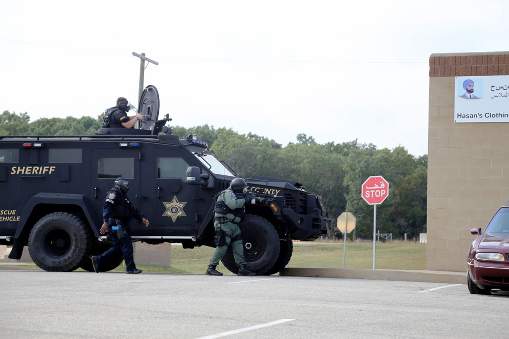 Wisconsin law enforcement personnel from several counties participate in a training scenario in September 2017 at the Combined Arms Collective Training Facility at Fort McCoy, Wisconsin. LMR is the first line of communication for all first responders, and recent efforts by PEO EIS will make the system easier to maintain—an important improvement since support for fielded LMR systems is not a primary duty on most Army installations. (U.S. Army photo by Scott T. Sturkol, Fort McCoy Public Affairs Office)