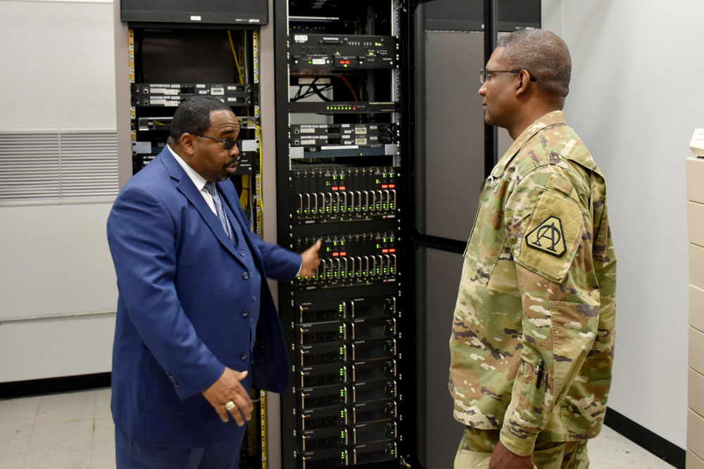 Ralph Edmonds, left, showcases a portion of Fort Belvoir's LMR equipment to Brig. Gen. Patrick W. Burden, program executive officer for Enterprise Information Systems (EIS). In 2014, PEO EIS' LMR Product Office began developing a plan to address a handful of threats to the readiness of Army LMR systems in the U.S., including a complex requirement, only two suppliers, and a shrinking pool of appropriated funds. (PM DCATS photo by James Christophersen)