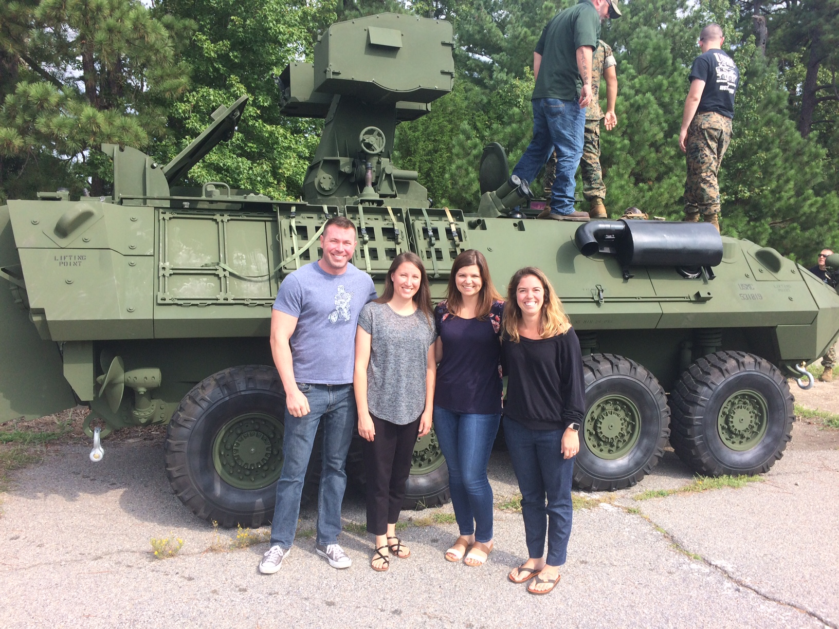 Staff Sgt. Michael Early, contract specialist; Emily Wood, purchasing agent; Rowley; and Xanthe Otterstedt, contracting officer; pose in front of a Marine tank for which they helped purchase training simulators. Photo by Paul Kopjoe, Marine Corps Program Manager for Light Armored Vehicles
