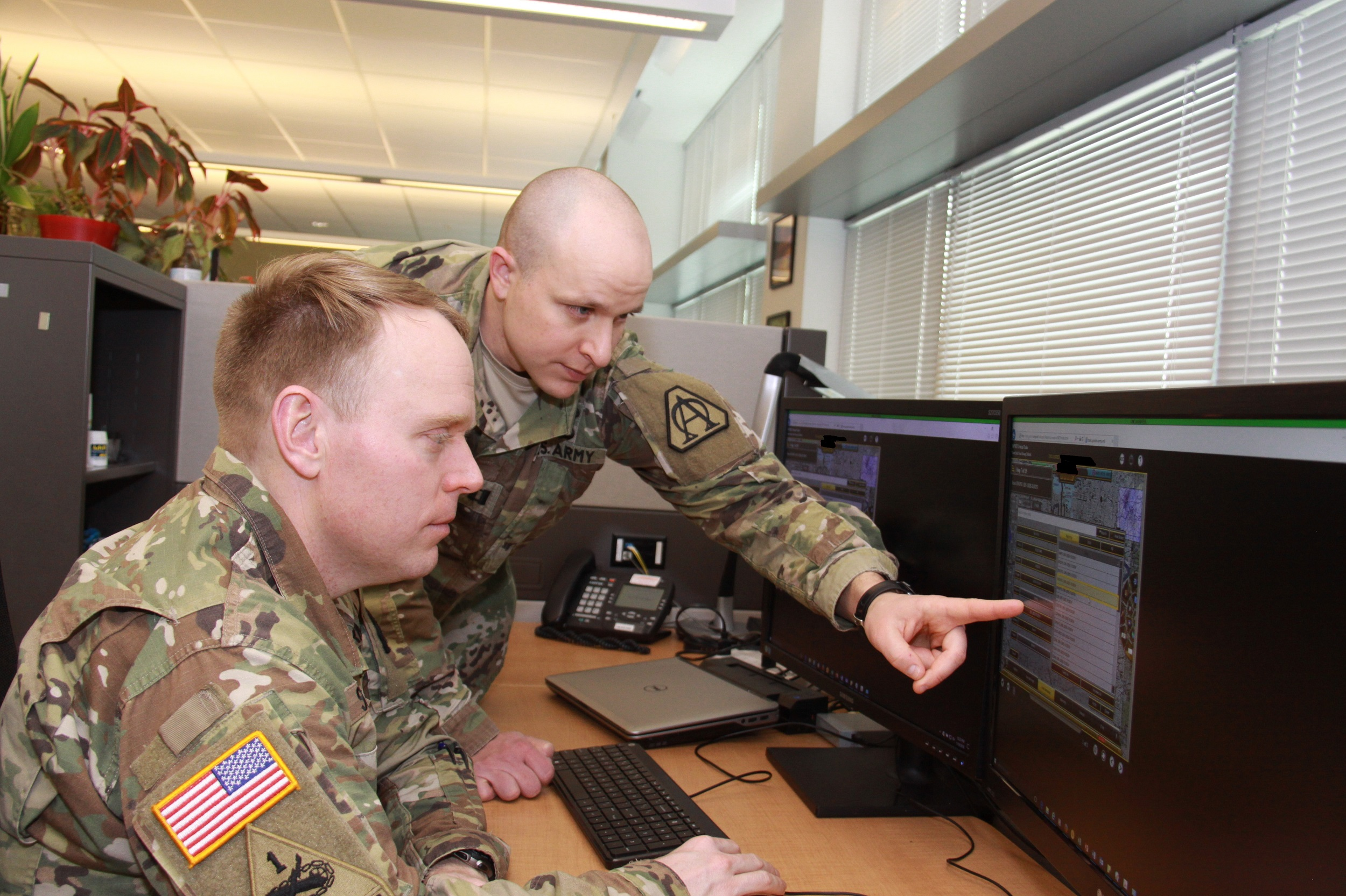 Capt. Doug Williams (standing) and Capt. Jake Singleton review the Joint Battle Command-Platform's new interactive multimedia instruction software at Aberdeen Proving Ground, Maryland, on Jan. 10, 2018. The IMI software will allow Soldiers to train on JBC-P from a CD, the Army's online training tool LandWarNet, or embedded on vehicle hardware known as Mounted Family of Computing Systems. (Photo Credit: Dan Lafontaine, PEO C3T Public Affairs)