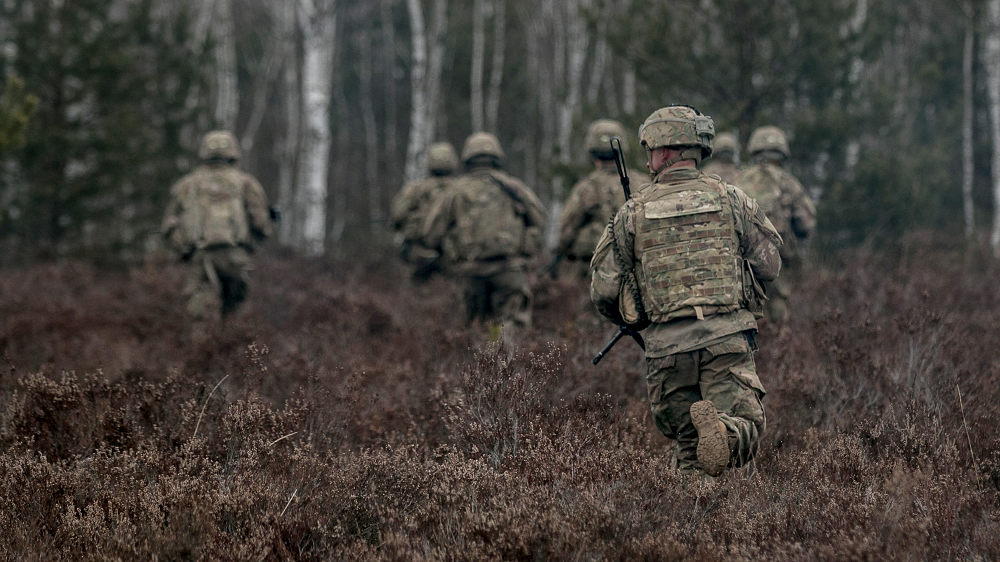 Soldiers assigned to 2nd Armored Brigade Combat Team, 1st Infantry Division, at Fort Riley, Kansas, move into nearby woods during a platoon combined arms live-fire exercise at Presidenski Range in Trzebian, Poland, March 26. The author, who was program manager of the search for a new camouflage pattern, explains that there are two ways to go wrong with test and evaluation: Cutting back on testing too aggressively, in pursuit of cost savings, puts the program at risk, while demanding more expensive field testing in the mistaken belief that it's more accurate drives the budget up. (U.S. Army photo by Spc. Dustin D. Biven, 22nd Mobile Public Affairs Detachment)