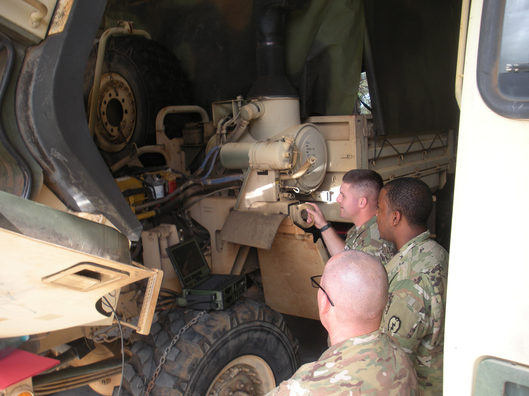 Soldiers from 25th Transportation Company utilizing diagnostics tools and software on M1083 FMTV, Schofield Barracks, HI, December 2015. Photo by Mr. Jesse Fields, AMSAA Operational Sustainment Analysis Team.