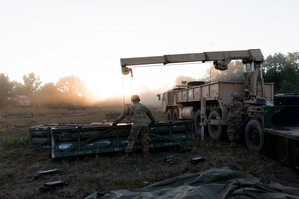 Spc. Cody Jensen, truck driver, 147th Forward Support Company, 1st Battalion, 147th Field Artillery Regiment, Roslyn, S.D., guides an expended missile tube from a Multiple Launch Rocket System onto an empty truck bed as Pfc. Steven Smith, truck driver, 147th FSC, operates the winch system on Aug. 10, 2018. South Dakota Army National Guard Soldiers are participating in Northern Strike, a joint multinational combined arms live fire exercise at Camp Grayling, Mich. (U.S. Army National Guard photo by Spc. Joshua Boisvert)