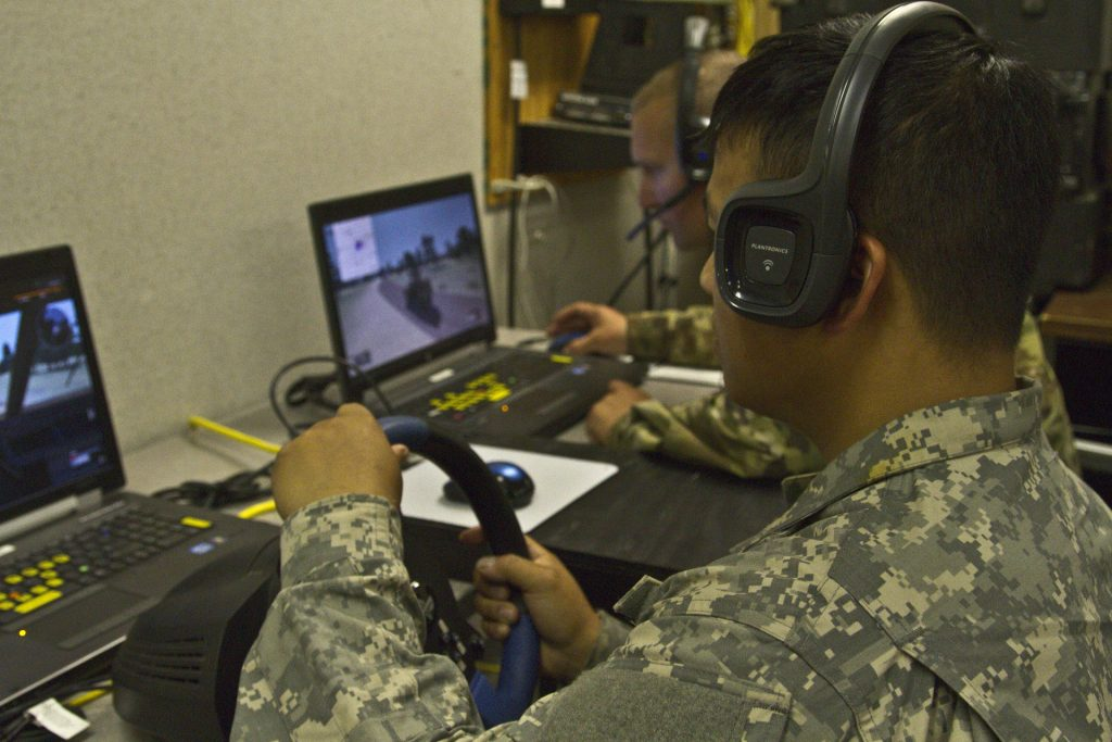 Army Reserve Soldiers Sgt. Cheng Thoa, left, and Sgt. Shawn Christensen with the 353rd Transportation Company out of Buffalo, Minnesota practice convoy operations on a virtual battlespace simulator on Fort McCoy, Wisconsin Aug. 7. (U.S. Army Reserve Photo by Staff Sgt. Anaidy G. Claudio)