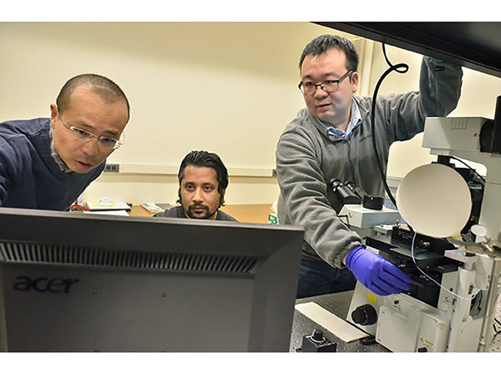 Cornell University Chemistry Professor Peng Chen, left, principal investigator in Army research that resulted in the first real-time visualization of single polymer chain growth, and Dr. Susil Baral, postdoctoral research associate, look at data while Dr. Chunming Liu, right, postdoctoral research associate, adjusts the microscope stage. In an example of the Army's collaboration with academia on technologies critical to battlefield success, scientists at Cornell, funded by the U.S. Army Research Laboratory, researched new analytical techniques for probing polymer dynamics and how to manipulate those dynamics to control polymer microstructure. (Photo courtesy of Cornell University)