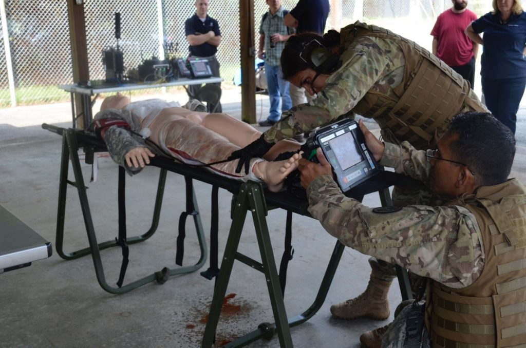 Field medics perform a simulated escharotomy using the Remote Diagnostic Technologies i2i Solution (Tempus Pro) at TATRC, Fort Detrick, Sept. 7. (Photo by Elizabeth Lamie, USAMRMC Public Affairs)