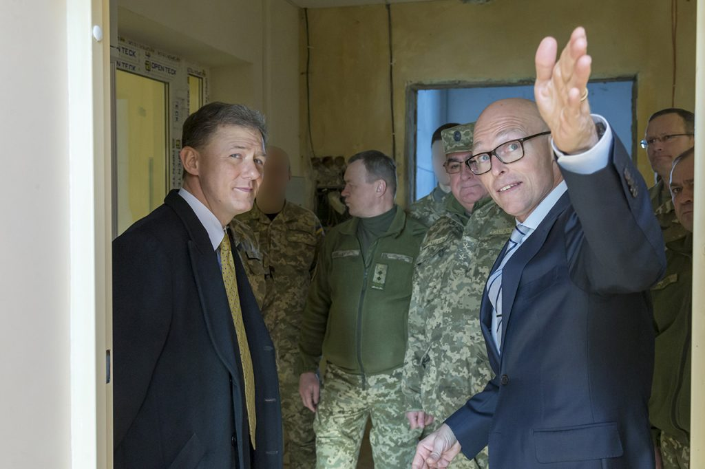 AIT Country Program Manager for Ukraine, Mr. Dan Hawkins (far right), briefing U.S. Deputy Ambassador to Ukraine, Mr. George Kent (left), and Ukrainian Deputy Chief of Defense, Lieutenant General Serhii Bessarab (center) on the new Ukranian Special Operations Forces training facilities (location in Ukraine undisclosed) being outfitted by AIT with various C4ISR and Defensive Cyber capabilities, January 2018. Photo credit: Mr. Jeremy Way, AIT support contractor